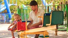 la petite fille dans des essais de hairtails à s'élever sur le père d'oscillation aide clips vidéos