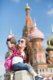 La petite fille dans des lunettes de soleil près de la séance de cathédrale Image libre de droits