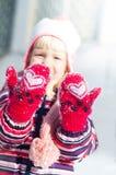 La petite fille dans des mitaines rouges avec le coeur blanc montre des mains photos libres de droits