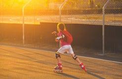 la petite fille dans des shorts blancs et un T-shirt rose patine sur le rôle du kah au coucher du soleil Photo stock