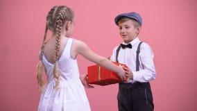 La petite fille dans donner blanc de robe a enveloppé actuel à l'ami, jour de valentines banque de vidéos
