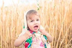 La petite fille dans l'écharpe se tient au milieu du champ et pleure Orphelins, problèmes sociaux Photo stock