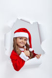 La petite fille dans l'équipement de Santa Claus donnant des thums lèvent le signe Photographie stock libre de droits