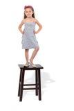 La petite fille dans la robe reste sur des selles Image stock