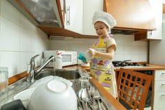 La petite fille dans le chapeau blanc de chef lave des plats Photographie stock