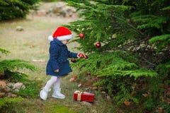 La petite fille dans le chapeau de Santa décore un arbre de Noël dans la forêt Image libre de droits
