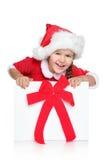 La petite fille dans le chapeau de Santa regarde hors du cadre de cadeau Photographie stock libre de droits