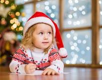 La petite fille dans le chapeau rouge de Noël écrit la lettre à Santa Claus Photos stock