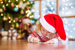 La petite fille dans le chapeau rouge de Noël écrit la lettre à Santa Claus Photographie stock