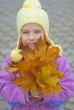 La petite fille dans le manteau jaune rassemble les feuilles jaunes d'érable Images stock