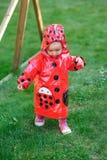 La petite fille dans le manteau rouge marche sur l'herbe Images libres de droits