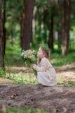 La petite fille dans la robe s'assied dans une forêt de pin Photos libres de droits