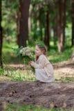 La petite fille dans la robe s'assied dans une forêt de pin Photo libre de droits