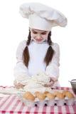 La petite fille dans un chapeau blanc de tablier et de chefs malaxent la pâte en Th Photos stock