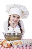 La petite fille dans un chapeau blanc de tablier et de chefs malaxent la pâte en Th Photo stock