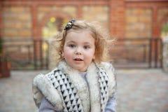 La petite fille dans un environnement urbain sourit à l'appareil-photo photos stock