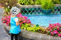 La petite fille dans une robe bleue regarde souhaitante la fontaine à B photo libre de droits