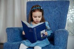 La petite fille dans une robe bleue s'assied dans un fauteuil bleu et est Photos libres de droits