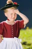 La petite fille dans une robe regarde dans le pays image stock