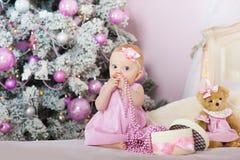 La petite fille dans une robe rose se reposant sur le lit et tire dedans ses perles de bouche pour le sapin An neuf Photo stock