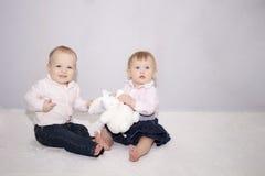 La petite fille de bébé garçon et de nourrisson jouant avec le grand lapin jouent Photo stock