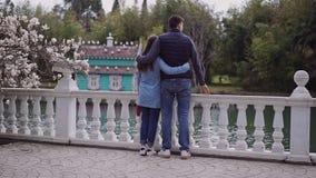 La petite fille de Fagile et un type grand marchent ensemble dans le jardin avec les magnolias de floraison le long du remblai banque de vidéos