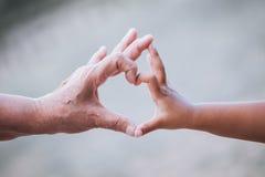 La petite fille de grand-mère et d'enfant faisant le coeur forment avec des mains Image stock