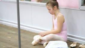 La petite fille de l'adolescence dans un collant de danseur rose, se prépare à la leçon de danse de ballet classique dans une éco clips vidéos