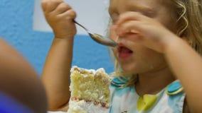 La petite fille de plan rapproché mange le morceau de gâteau d'anniversaire avec la cuillère de thé banque de vidéos