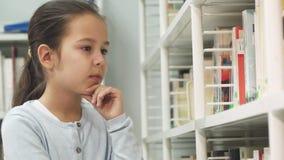 La petite fille de Prety souriant à la cueillette d'appareil-photo réserve à la bibliothèque banque de vidéos