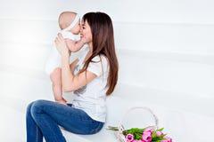 La petite fille de sourire de bébé mord sa brune de maman de nez dans le petit morceau Photographie stock libre de droits