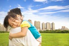 La petite fille de sourire dormant sur le père épaulent au parc de ville Images libres de droits