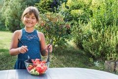 La petite fille de sourire est une salade végétale de agitation dans le jardin Images libres de droits