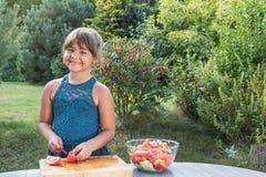 La petite fille de sourire fait cuire dans le jardin Images libres de droits