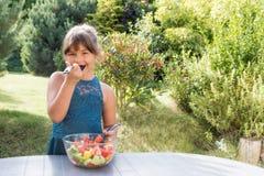La petite fille de sourire goûte la salade dehors Photos libres de droits