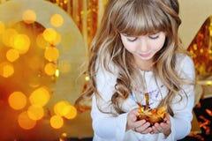 La petite fille de sourire heureuse tenant l'or s'allume dans des mains Photographie stock
