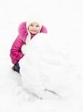 La petite fille de sourire mignonne fait le bonhomme de neige dans le jour d'hiver Images libres de droits