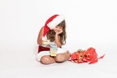 La petite fille de sourire regarde un cadeau inadéquat photographie stock libre de droits
