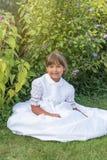 La petite fille de sourire s'asseyant dans la demoiselle d'honneur blanche vêtx Photographie stock