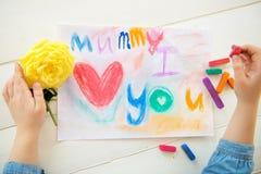 La petite fille dessine la carte postale pour le jour de mères Photo libre de droits