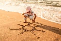 La petite fille dessine le soleil sur le sable à la plage Photographie stock