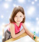La petite fille dessine le stylo feutre sur une surface blanche Image stock