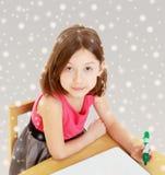 La petite fille dessine le stylo feutre sur une surface blanche Photo libre de droits
