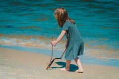 La petite fille dessine sur le sable à la plage Photographie stock libre de droits