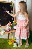 La petite fille dessine sur un tableau noir Photo stock