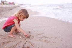 La petite fille dessine un soleil dans le sable sur le bord de la mer Image stock