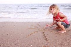 La petite fille dessine un soleil dans le sable sur le bord de la mer Photo stock