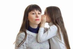 La petite fille dit quelque chose à son plan rapproché d'oreille du ` s de mère Image libre de droits