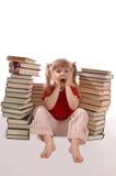 La petite fille doit afficher beaucoup de livres Photo stock