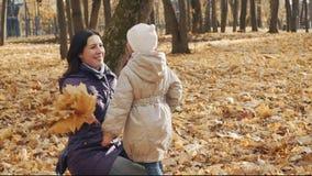 La petite fille donne à maman un bouquet des feuilles d'automne en parc banque de vidéos